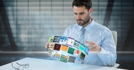 Digital composite of Businessman looking at panels spinning on desk Stock Photo