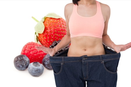 midsection: Digital composite of Midsection of woman in loose jeans by fruits representing weight loss concept