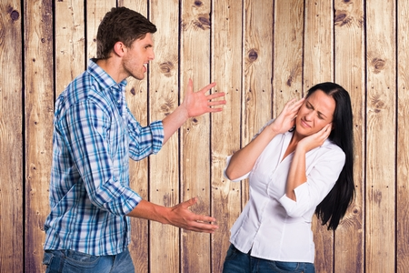 Digital composite of Angry man arguing with woman against wooden wall Stock Photo