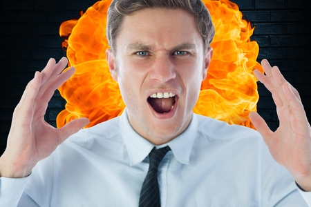 Digital composite of Close-up of angry businessman shouting against fire Stock Photo