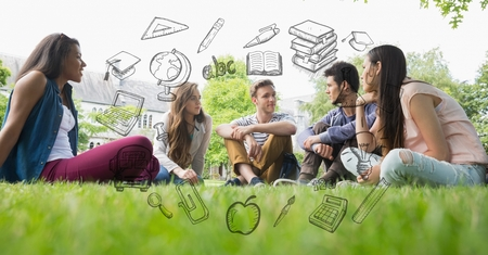 Digital composite of Male and female students sitting on grass with educational graphics Stock Photo