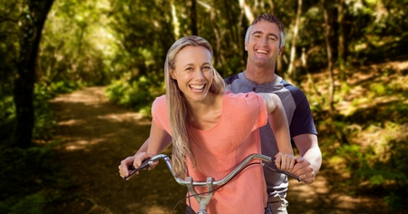 Digital composite of Happy couple riding cycle in forest