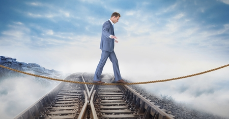 Digital composite of Digital composite image of businessman walking on rope over railway tracks