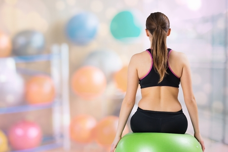 Digital composite of Rear view of woman sitting on fitness ball at gym Stock Photo