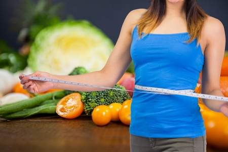 midsection: Digital composite of Midsection of woman measuring waist with vegetables in background