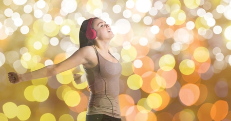 Digital composite of Female music artist wearing headphones over bokeh Stock Photo