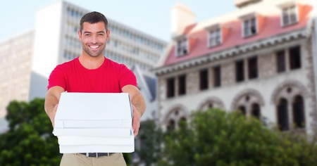 residential tree service: Digital composite of Portrait of smiling delivery man holding pizza boxes against buildings
