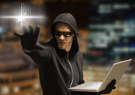 night out: Digital composite of Criminal in hood on laptop in front of night city Stock Photo