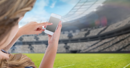 Digital composite of Woman touching blank screen of mobile phone at stadium