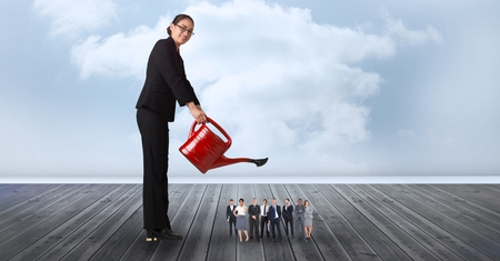 cowering: Digital composite of Smiling businesswoman watering employees on pier against cloudy sky