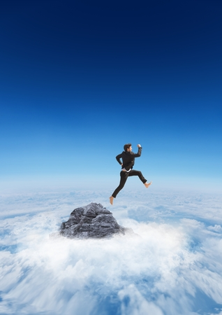 Business man jumping off mountain peak in the clouds