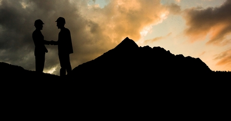 bowed head: Digital composite of Silhouette male architects shaking hands on mountain against cloudy sky during sunset