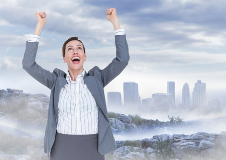 Digital composite of Business woman cheering on mountain against misty skyline Stock Photo