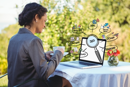 Digital composite of Businesswoman having coffee while looking at laptop with diagrams Stock Photo