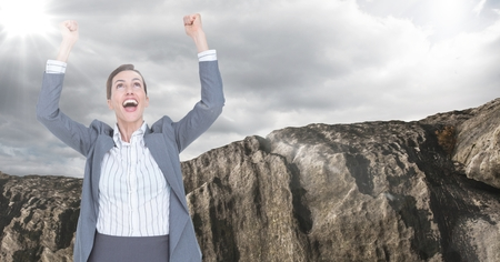 euphoria: Digital composite of Business woman cheering with flare against rock and cloudy sky