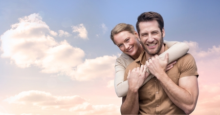 Digital composite of Portrait of smiling couple embracing against cloudy sky Stock Photo