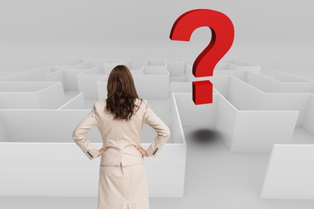 Digital composite of Rear view of businesswoman with hands on hips looking at question mark over maze Stock Photo