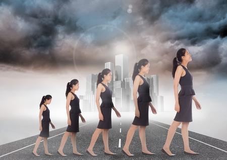statics: Digital composite of Walking woman growing enlarging on road to city Stock Photo