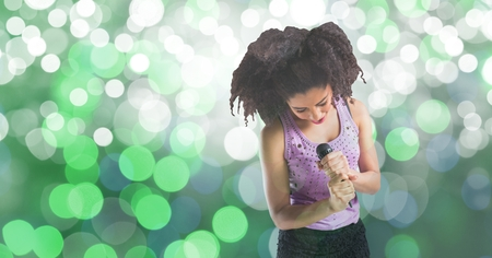 Digital composite of Young woman singing into microphone against bokeh background