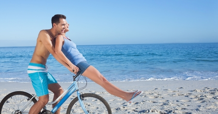 Digital composite of Carefree couple riding cycle at beach
