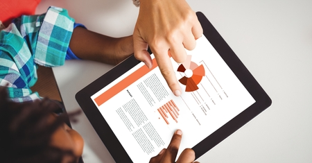 Digital composite of Business people discussing over graphs on digital tablet Stock Photo