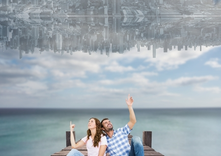 sit down: Digital composite of up side down city in the sky over the sea with couple sit on a dock and looking up
