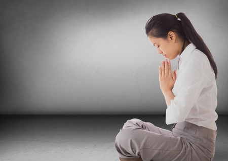 cross legged: Digital composite of Business woman with praying in grey room