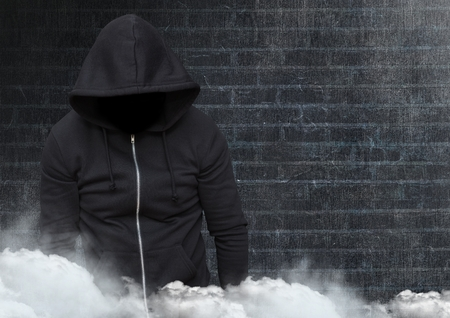 Digital composite of Anonymous criminal in hood in front of brick wall