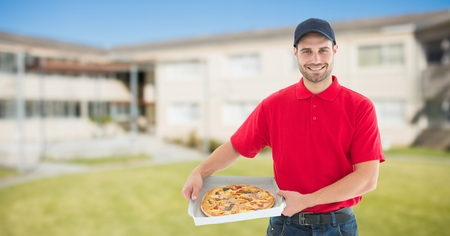 standing stone: Digital composite of Portrait of smiling delivery man holding pizza boxes against buildings