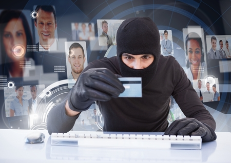 Digital composite of Criminal in hood on laptop with card in front of peoples profile faces Stock Photo