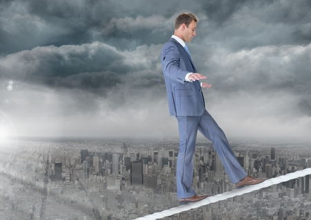 Digital composite of Walking businessman on tightrope over city and clouds