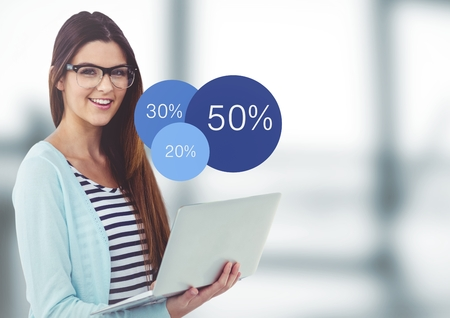 Digital composite of Woman with laptop and blue statistics in blurry grey office Stock Photo