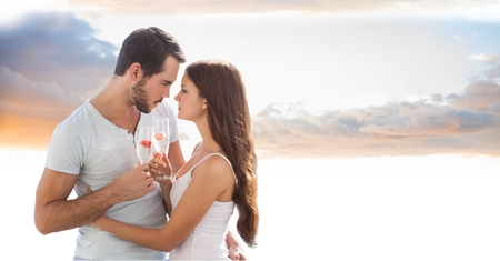 dating strategy: Digital composite of Romantic couple toasting champagne flutes against sky Stock Photo