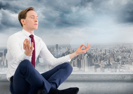handsome men: Digital composite of Business man with meditating against grey skyline and clouds Stock Photo