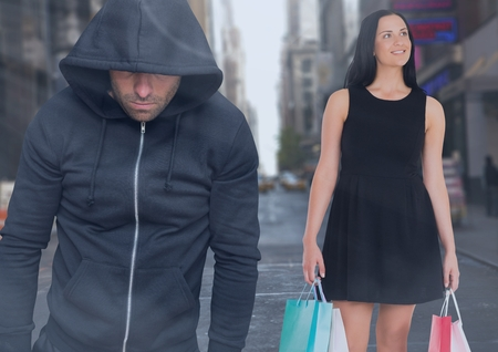 Digital composite of Criminal in hood in front of city street and Walking woman with shopping bags Stock Photo
