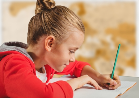 Digital composite of Girl doing homework against blurry brown map Stock Photo