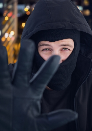 illuminated: Digital composite of Criminal in hood in front of night city Stock Photo