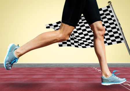 Digital composite of Runner legs on track against yellow background and checkered flag Stock Photo