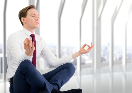 Digital composite of Business man meditating against blurry white window