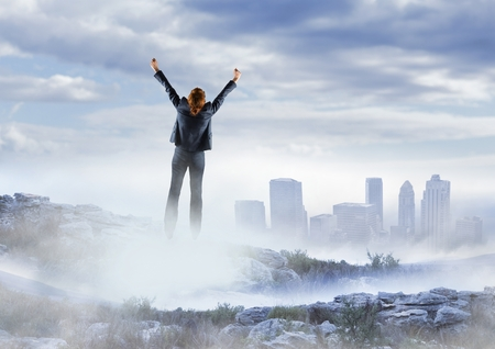 euphoria: Digital composite of Business woman cheering on misty mountain peak against skyline Stock Photo