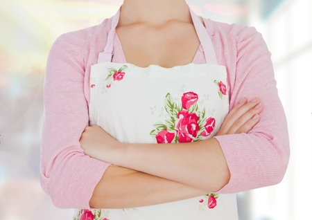 Digital composite of woman with flowers aprol, hand folded. kitchen