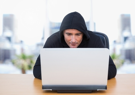 Digital composite of Criminal in hood on laptop by windows