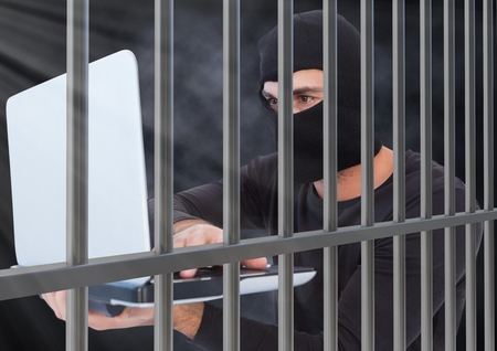 interned: Digital composite of Criminal in balaclava with laptop behind prison bars Stock Photo