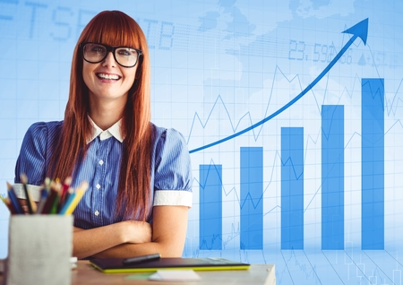 Digital composite of Woman at desk with arms folded against blue graph Stock Photo