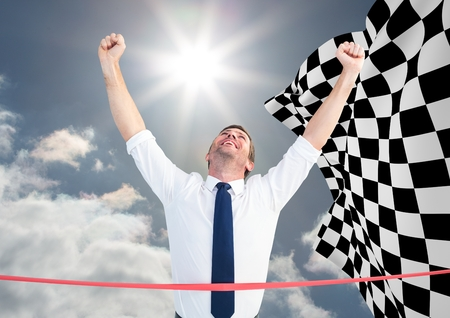 Digital composite of Business man at finish line against sky and checkered flag Stock Photo