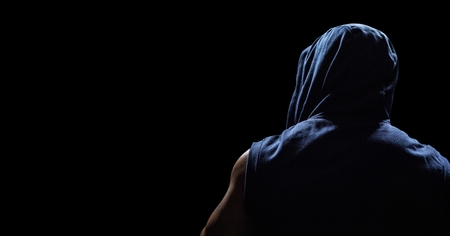 Digital composite of Back of man in hoodie against black background Stock Photo