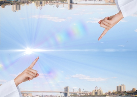 Digital composite of up side down city with light in the middle of the sky. hand fingering Stock Photo