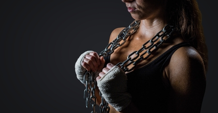 Digital composite of Woman with chains against dark grey background Stock Photo
