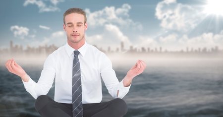Digital composite of Business man meditating against water and blurry skyline with flare Stock Photo