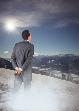 snowcapped mountain: Digital composite of Business man with mist standing looking at mountains